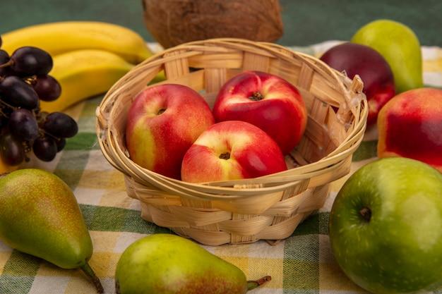 Vista cercana de frutas como melocotón en canasta y coco plátano pera uva en tela escocesa sobre fondo verde