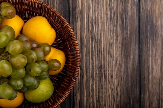 Vista cercana de frutas como pluot verde uva y nectacots en canasta sobre fondo de madera con espacio de copia