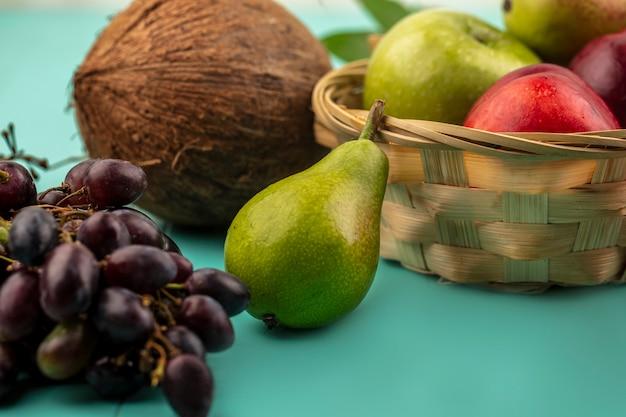 Vista cercana de frutas como uva pera coco y canasta de manzana melocotón sobre fondo azul.