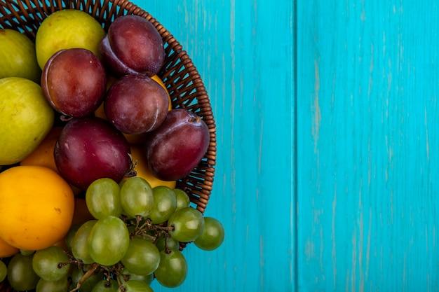 Vista cercana de frutas como uva pluots nectacots en canasta sobre fondo azul con espacio de copia