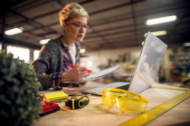 Vista cercana de gafas de taller amarillas frente a ingeniera con anteojos trabajando con planos y computadora portátil en el taller