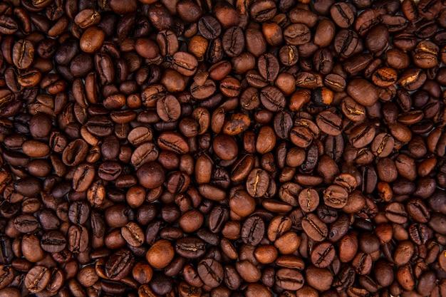 Vista cercana de granos de café tostados frescos oscuros sobre fondo de granos de café