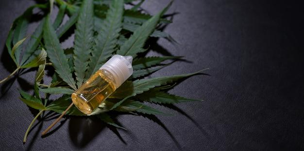Vista cercana de hojas de marihuana y botellas de aceite de cannabis