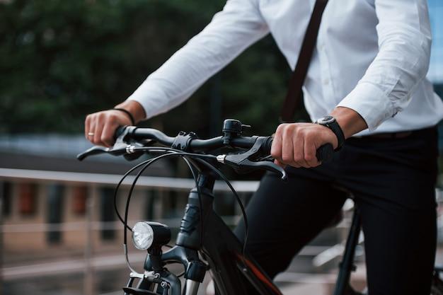 Vista cercana. hombre de negocios en ropa formal con bicicleta negra está en la ciudad.