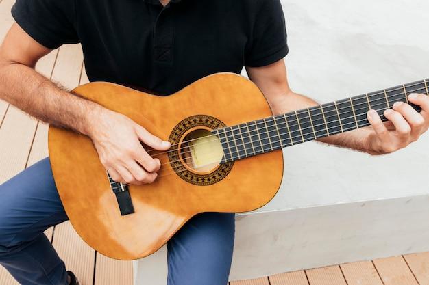 Vista cercana del hombre que sostiene una guitarra