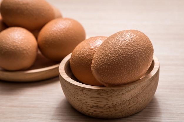 Vista cercana de huevos de gallina sobre fondo de mesa de madera
