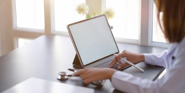 Vista cercana de joven doctora escribiendo cartas médicas con tableta en la sala de oficina