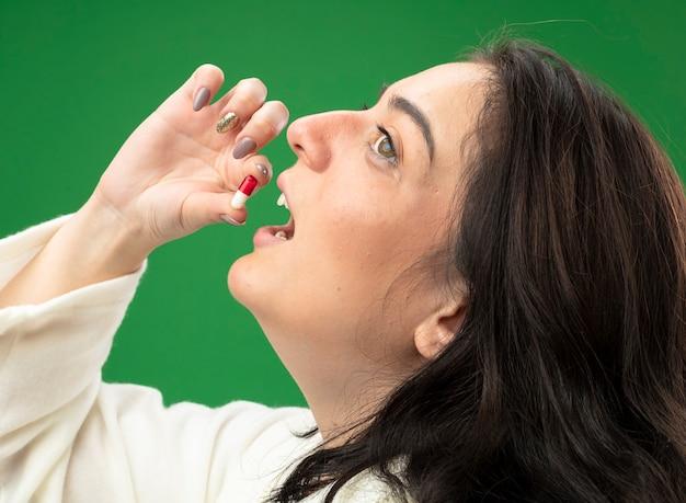 Vista cercana de la joven enferma vistiendo bata de pie en la vista de perfil tomando la píldora mirando al lado aislado en la pared verde