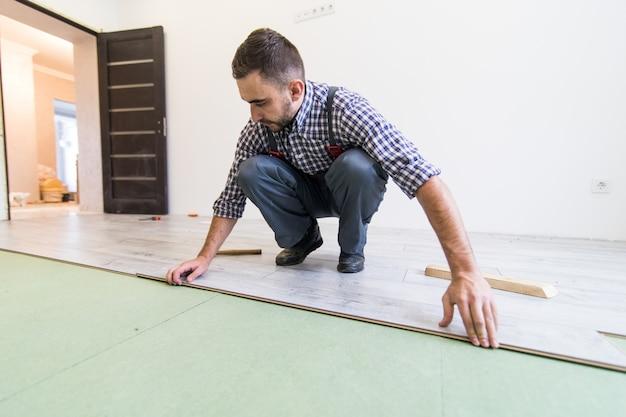 Vista cercana del joven trabajador colocando un piso con tablas de piso laminado