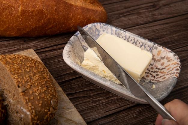 Vista cercana de kinfe cortando mantequilla y panes alrededor sobre fondo de madera