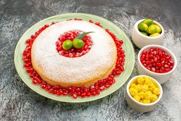Vista cercana de lado pastel y dulces un pastel y tazones de semillas de granada dulces de frutas cítricas