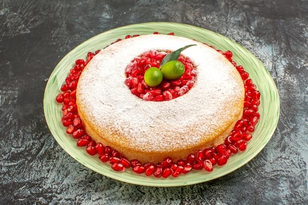 Vista cercana de lado pastel con granada un apetitoso pastel con granada y frutas cítricas