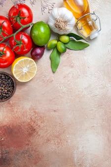 Vista cercana lateral aceite de tomates cítricos tomates cebolla ajo limón pimienta negra