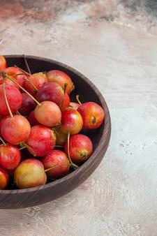 Vista cercana lateral cerezas cuenco de madera de las apetitosas cerezas en la mesa de color gris crema