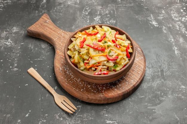 Vista cercana lateral ensalada ensalada de verduras en el recipiente marrón en el tenedor de madera de tablero de cocina