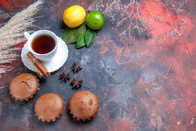 Vista cercana lateral pastel de frutas cítricas con hojas de los apetitosos cupcakes una taza de té