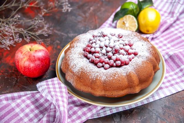 Vista cercana lateral de un pastel un pastel con frutos cítricos de grosellas rojas sobre el mantel a cuadros de manzana
