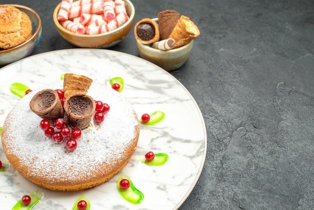 Vista cercana lateral un pastel un pastel con gofres grosellas rojas salsa verde tazones de dulces