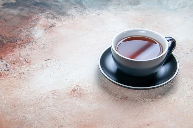 Vista cercana lateral de una taza de té negro taza de té en el platillo