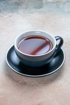 Vista cercana lateral una taza de té una taza de té en el platillo negro