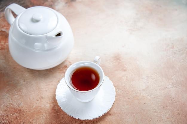 Vista cercana lateral una taza de té tetera blanca una taza de té