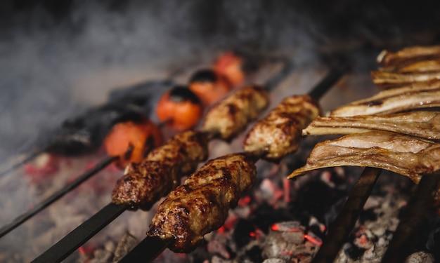 Vista cercana de lula kebab en brochetas de metal en la pared oscura