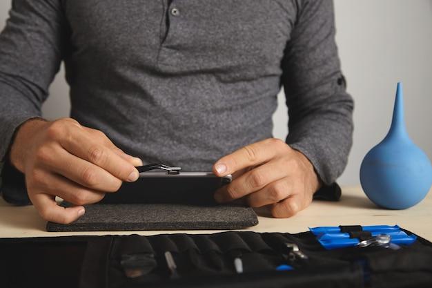 Vista cercana, el maestro usa la herramienta pincher para quitar la ranura de la tarjeta sim del teléfono inteligente mientras lo desmonta