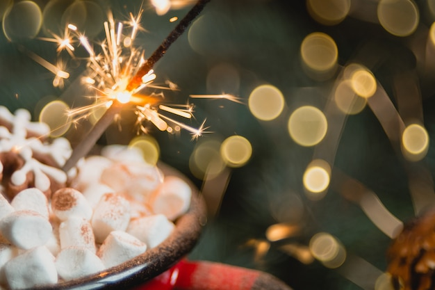 Vista cercana de malvavisco en taza roja con bengala. enfoque selectivo suave. bokeh de fondo abstracto, copyspace. composición de navidad o año nuevo.