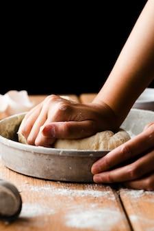 Vista cercana de la mano haciendo masa en una bandeja