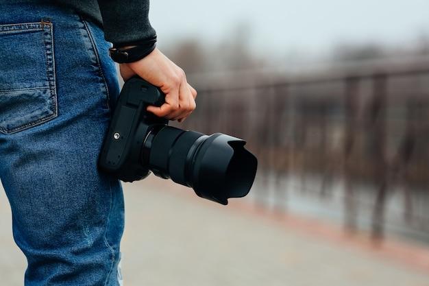Vista cercana de la mano masculina que sostiene la cámara profesional en la calle.