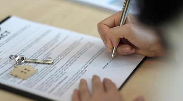 Vista cercana de las manos del empresario que firma los documentos del hogar de arrendamiento y tiene las llaves del apartamento en el papeleo