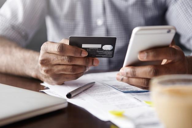 Vista cercana de las manos del hombre africano con tarjeta de crédito de plástico y smartphone