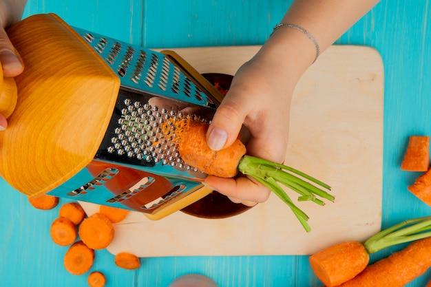 Vista cercana de manos de mujer rallar zanahoria en rallador de metal con tabla de cortar y zanahorias sobre fondo azul.