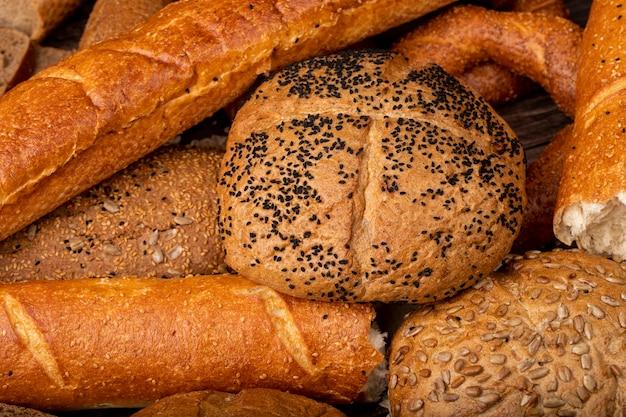 Vista cercana de la mazorca de semillas de amapola con baguette y otros panes