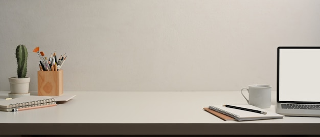 Vista cercana de la mesa de trabajo con computadora portátil, cuadernos, material de oficina y espacio para copiar en la sala de la oficina en casa