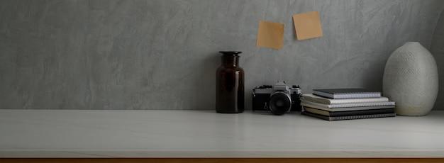 Vista cercana de la mesa de trabajo moderna con cámara, libros, decoración y espacio de copia