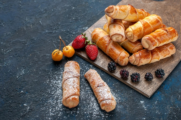 Vista cercana de la mitad superior deliciosos brazaletes dulces con relleno delicioso horneado con frutas en un escritorio oscuro, hornear pastel galleta postre dulce de azúcar