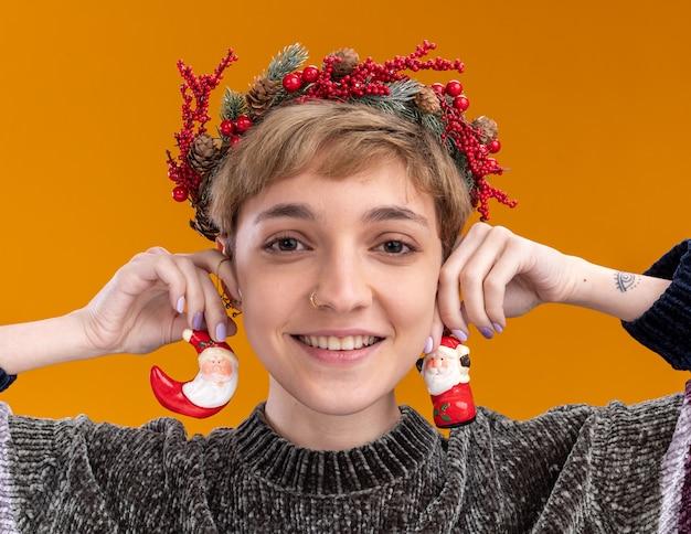 Vista cercana de la niña bonita joven sonriente con corona de cabeza de navidad colgando adornos navideños de santa claus en las orejas mirando a cámara aislada sobre fondo naranja