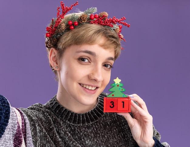 Vista cercana de la niña bonita joven sonriente con guirnalda de cabeza de navidad sosteniendo el juguete del árbol de navidad con fecha mirando a cámara aislada sobre fondo púrpura