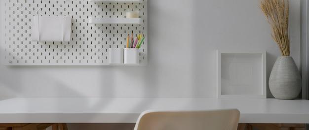 Vista cercana de la oficina en casa mínima con decoraciones y copia espacio en la mesa blanca