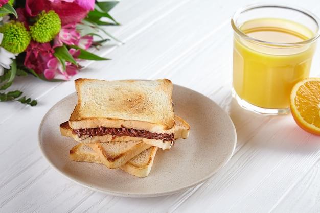 Vista cercana de pan tostado con mantequilla de maní y jugo de naranja
