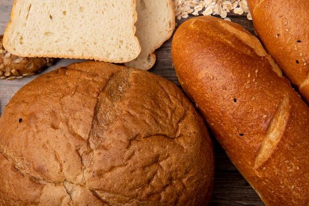 Vista cercana de panes como mazorca y baguette con rebanadas de pan blanco sobre fondo de madera