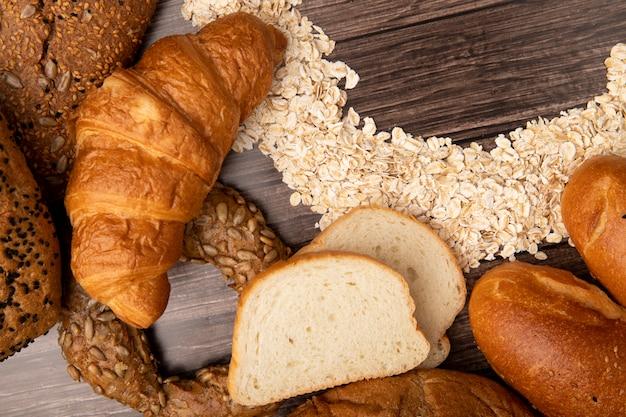 Vista cercana de panes como pan japonés de mantequilla pan blanco con copos de avena sobre fondo de madera
