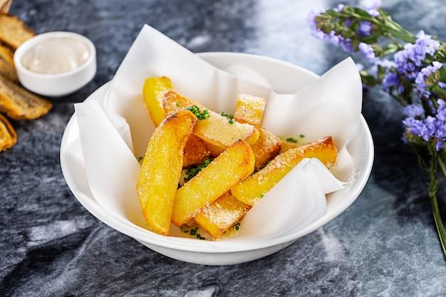 Vista cercana de papas fritas con salsa, ajo y queso en papel artesanal