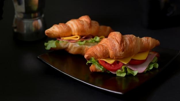 Vista cercana de un plato de comida de desayuno con cruasán fresco sandwich jamón y queso