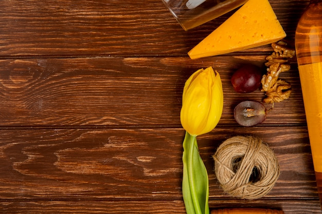 Vista cercana de queso cheddar y nuez con trozos de uva y hilo sobre fondo de madera decorado con flores con espacio de copia
