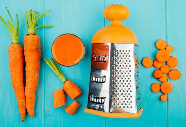 Vista cercana del rallador de metal con jugo de zanahoria y zanahorias en rodajas enteras cortadas sobre fondo azul.