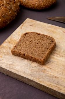 Vista cercana de la rebanada de pan de centeno en la superficie de madera y fondo marrón