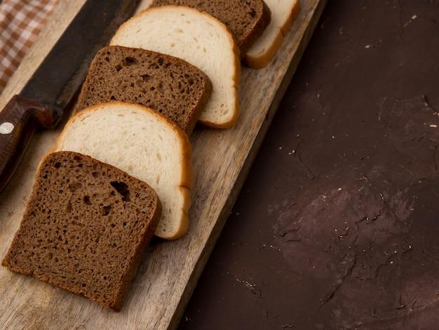 Vista cercana de rebanadas de pan blanco y negro con cuchillo sobre superficie de madera y fondo granate con espacio de copia