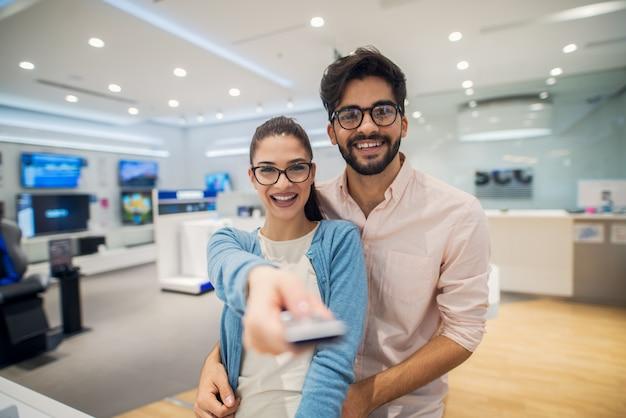 Vista cercana del retrato de hipster feliz emocionado atractivo joven amor romántico pareja romántica de pie abrazado mientras niña apuntando con el control remoto a la cámara en una tienda de tecnología.
